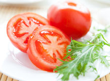Big red tomato on a white plate and lettuce Royalty Free Stock Images