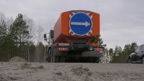 Big red truck with arrow road sign turning on road with cars. Rear view of big carriage car on construction stock video