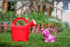 Big red Watering can and small pink stock photography