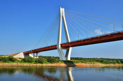 A big red and white bridge through the river Royalty Free Stock Photo