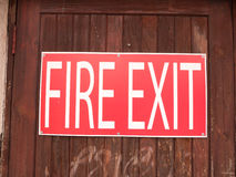 A big red and white sign outside on a fence saying fire exit woo Stock Images