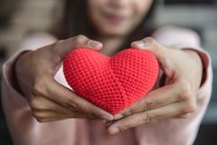Big red yarn heart holding and giving to front by woman hand. Lo. Ve and affection in Valentines day concept. Romantic object and health care stock photography