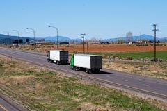 Big rig semi trucks convoy with semi trailers going on straight. Big rig American classic fleet semi trucks convoy with semi trailers going on straight divided Royalty Free Stock Images