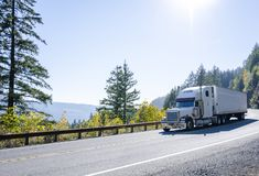 Big rig white classic semi truck transporting cargo in refrigerated semi trailer on winding autumn road. Big rig American powerful white classic semi truck stock photography