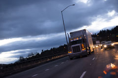 Big rig american semi truck tractor on highway in twilight. A classic huge powerful big rig semi truck with a long reefer trailer for the transportation of Royalty Free Stock Photos