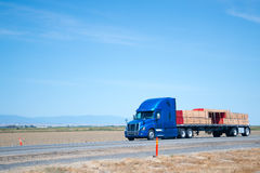 Big rig blue semi truck with flat bed trailer transporting lumbe Stock Photography