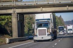 Big rig classic semi truck with covered semi trailer driving on the road under the bridge in front of semi trucks convoy. Big rig bright dark classic American stock image