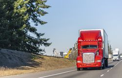 Big rig bright red classic American idol semi truck with reefer semi trailer driving on the straight highway in sunny day. Big rig bright red classic American royalty free stock photos