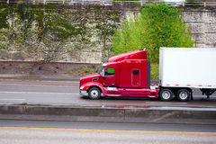 Big rig bright red semi truck with dry van semi trailer moving o. A side view of a large bright red American semi truck with a raised cab and sleeping place for royalty free stock images