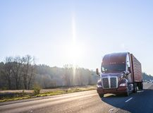 Big rig brown semi truck transporting container moving on the highway at sunshine day. Big rig American professional popular long haul brown bonnet semi truck royalty free stock image