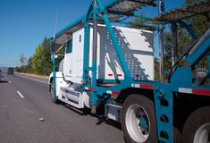 Big rig car hauler semi truck with two level trailer for transpo. White Big rig American professional car hauler semi truck with two level trailer for Royalty Free Stock Photo