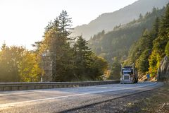 Big rig classic semi truck transporting cargo on the winding autumn road in Columbia River Gorge. Big rig classic American idol bonnet dark semi truck with tall royalty free stock photography