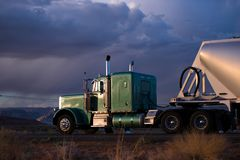 Big rig semi truck with bulk semi trailer carries cargo on the A. Big rig classic green semi truck with capacity compartment behind of tractor cab transporting Royalty Free Stock Photo