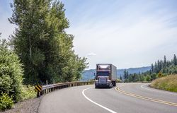 Big rig dark classic semi ruck with semi trailer moving on the turning curve road with trees on the side. Big rig red powerful American bonnet long haul semi stock images