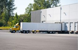 Big rig day cab semi trucks for local deliveries loading and unloading commercial cargo in warehouse dock. A huge number of big rig semi trucks are loaded and royalty free stock photography