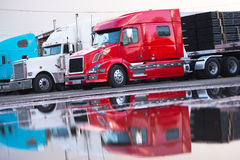 Big rig modern semi truck flat bed trailer with cargo on parking Royalty Free Stock Images
