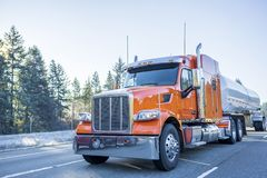Big rig orange classic American semi truck transporting liquid cargo in tank semi trailer moving on the winter frosty road. Industrial Big rig low cab bonnet royalty free stock image