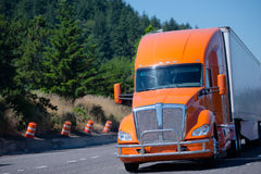 Big rig orange semi truck and trailer running on green highway w Stock Photo