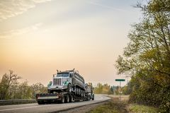 Big rig semi truck transporting oversized tip truck on step down semi trailer on winding evening road royalty free stock photos