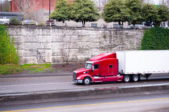 Big rig red semi truck with dry van semi trailer going down on h. A profile of a huge red American big rig semi truck with a raised cab with spoiler for the Royalty Free Stock Photos
