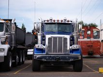 Big rig semi tipper truck for construction and landscaping work. Powerful heavy-duty semi trucks washed after work day on the transportation of construction Stock Photos