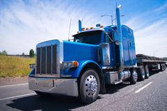 Big rig semi truck blue wolf of roads. Classic blue bonneted big rig semi truck with chrome accessories and details on a multilane highway road with a laden flat Royalty Free Stock Images