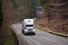 Big rig semi truck with bulk semi trailer moving by winding road. Big rig semi truck tractor with spoiler transporting commercial cargo in bulk semi trailer royalty free stock photography