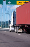 Big rig semi truck with container on flat bed trailer driving on Stock Image