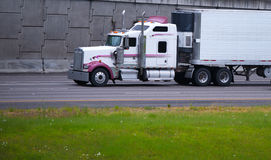 Big rig semi truck custom built with reefer trailer unit on road. Classic big rig semi truck with color accents on fenders and spoiler and high tailpipes pulling Royalty Free Stock Image