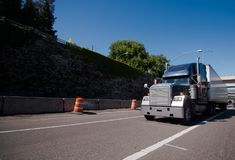 Big rig semi truck with dry van trailer running on wide highway. A modern large dark big rig semi truck with a dry van semi trailer delivers an industrial cargo royalty free stock photography
