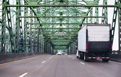 Big rig semi truck with lifting back door unit going highway alo. Big rig white semi truck with box trailer and lifting unit under back door going on interstate Stock Photos