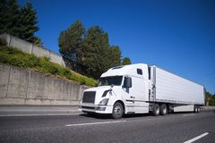 Big rig semi truck with reefer semi trailer going on highway wit. White modern Big rig semi truck with reefer semi trailer equipped with refrigeration unit going Royalty Free Stock Photo