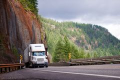 Big rig semi truck with reefer trailer transporting cargo on win. Big rig semi truck with refrigeration trailer transporting cargo moving on the bridge on a Royalty Free Stock Images
