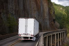 Big rig semi truck with refrigerator semi trailer moving on bridge on side of big rock wall in Columbia Gorge. Big rig semi truck with long refrigerator semi stock photo