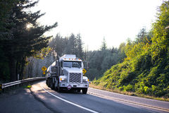 Big rig semi truck with tank trailers on winding road in forest. Large American professional powerful rig semi truck carries two fuel trailers tanks, or Royalty Free Stock Image