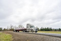 Big rig semi truck transporting fastened commercial cargo on flat bed semi trailer going on the road in overcast weather. Big rig American professional popular royalty free stock photos