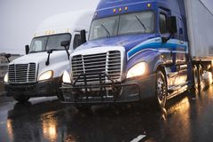 Big rig semi trucks going in rain side by side on evening highway. Heavy traffic with big rig semi trucks convoy going e by e with semi trailers transporting stock images