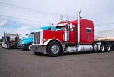 Big rig semi trucks stand in row on parking lot. Powerful heavy-duty big rig red and blue classic and modern semi trucks with flat bed trailers  are parked in an Stock Photo