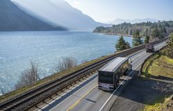 Big rig semi trucks with trailers convoy running on the highway along the Columbia River. Big rig long haul bonnet American semi truck transporting commercial royalty free stock photography