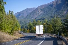 Big rig semi trucks with semi trailers drive towards each other on the winding mountain road. Big rig professional commercial semi trucks with semi trailers stock photos