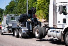 Big rig towing semi truck tow ather semi truck tractor on the road. A powerful big rig semi truck tractor tows a broken white semi truck on a highway with green royalty free stock photos