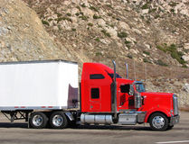 Big Rig Tractor Trailer Truck on a Mountain Road. Big rig red tractor truck with white trailer on mountain road parking lot with rocky cliff Stock Images