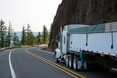 Big rig white semi truck with bulk covered semi trailer running. Big rig white American model bonnet semi truck tractor with plastic covered long bulk semi royalty free stock photos