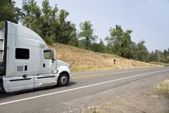 White big rig semi truck with break the air aerodynamic accessories running on the road with trees. Big rig white semi truck with dry van full size semi trailer stock photos
