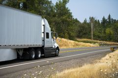 Long haul white big rig semi truck with semi trailer transporting commercial cargo on the road. Big rig white semi truck with dry van full size semi trailer with royalty free stock images