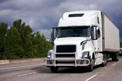 Big rig white semi truck with grille guard and trailer on the ro Stock Photos