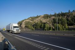 Big rigs semi trucks convoy running on turning highway with rock stock images