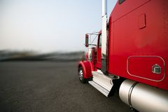 Bright red classic big rig semi truck with chrome pipe and filter running on the wide road royalty free stock image