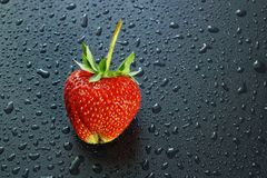 Big ripe berry red strawberry on a dark background water drops c. Opy space for text and logo Stock Photo