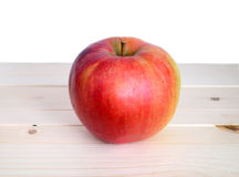 Big ripe red apple in beige wooden shelf closeup Stock Images